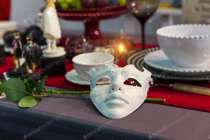 Christmas table decorated with mask and flower