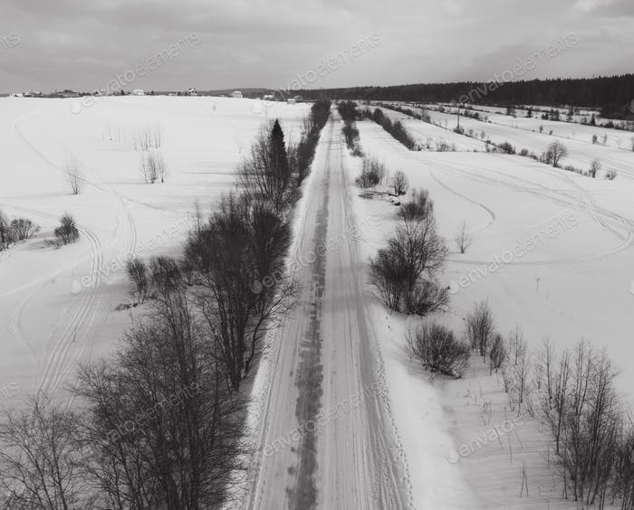 Aerial view of snow winter country road black and white photo