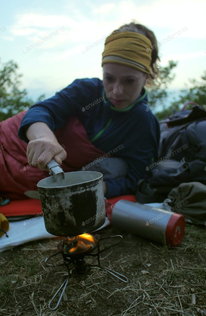 female hiker cooking outdoors