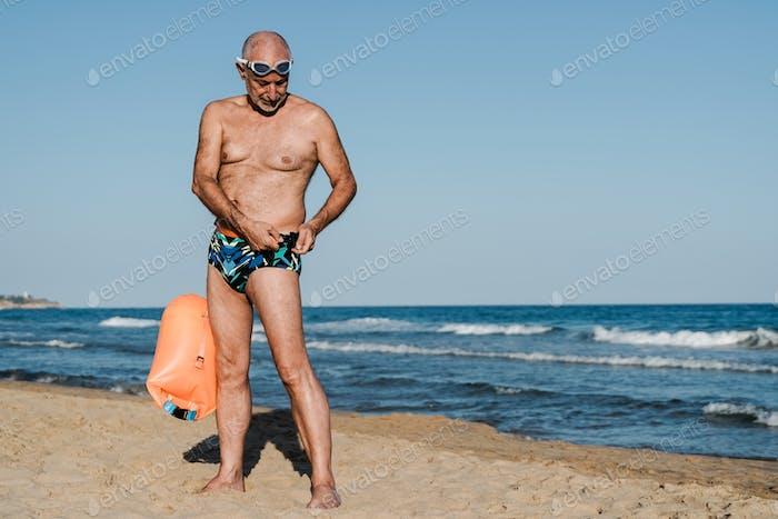Sport senior swimmer man training to swim open water triathlon with beach on background