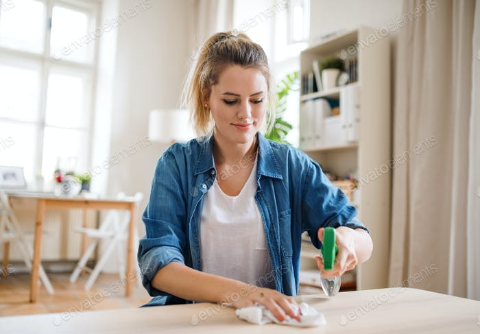 Young woman indoors at home, cleaning table.