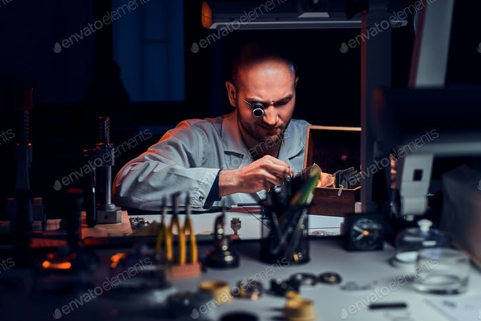 Focused man is working at his workshop with monocle and other tools repairing old watches