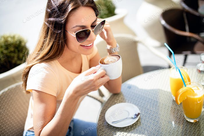 Portrait of happy young woman holding coffee in cafe outdoor