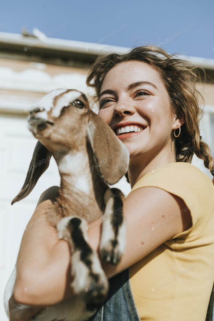 Portrait of a beautiful young woman with a goat