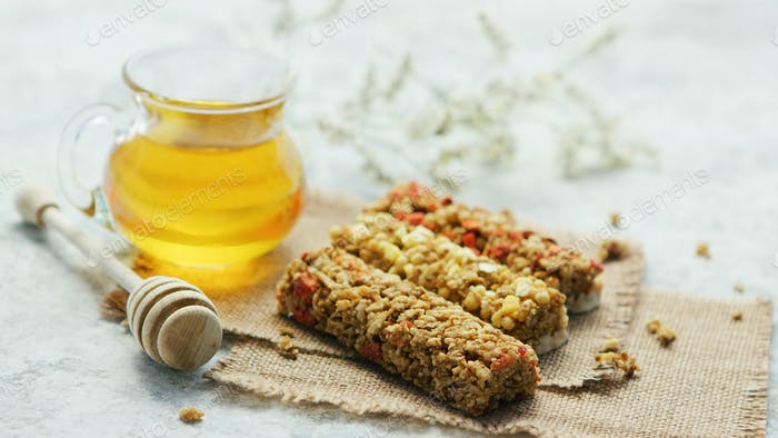 Delicious cereal bars and honey in jar