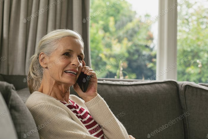 Active senior Caucasian woman sitting on sofa and talking on mobile phone in living room