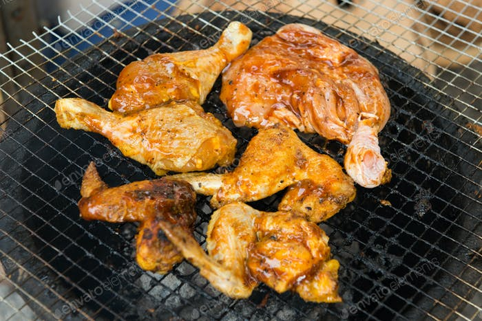 BBQ chicken meat roasted on hot flaming charcoal grill