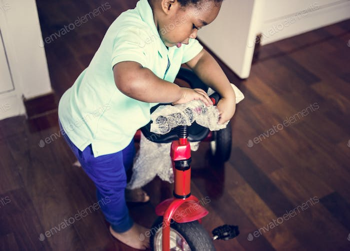 Black kid unwrapping the bicycle