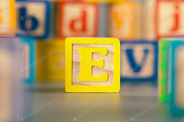 Fotografía del colorido bloque de madera letra E