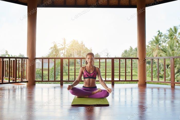 Young woman meditating in lotus yoga pose