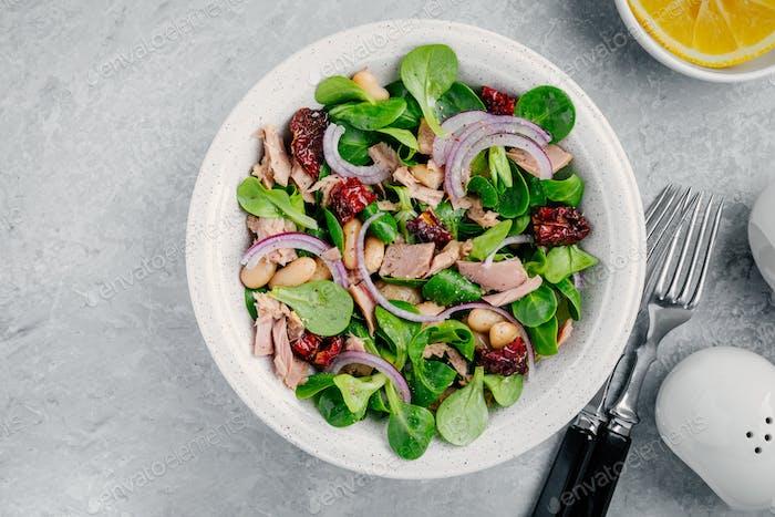Salat mit weißen Bohnen, Thunfisch, roten Zwiebeln und getrockneten Tomaten mit grünen Salatblättern