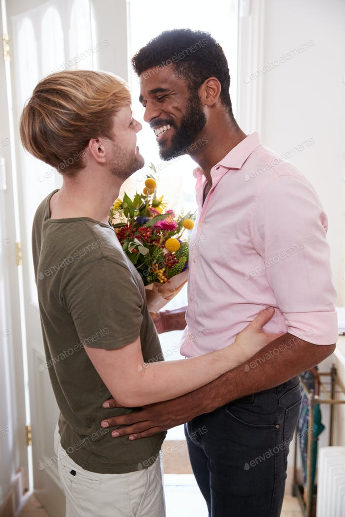 Man Opening Front Door To Gay Partner At Home Who Gives Him Bunch Of Flowers