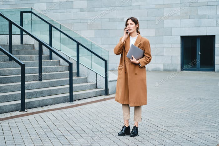 Young attractive businesswoman in coat with laptop confidently talking on cellphone on city street