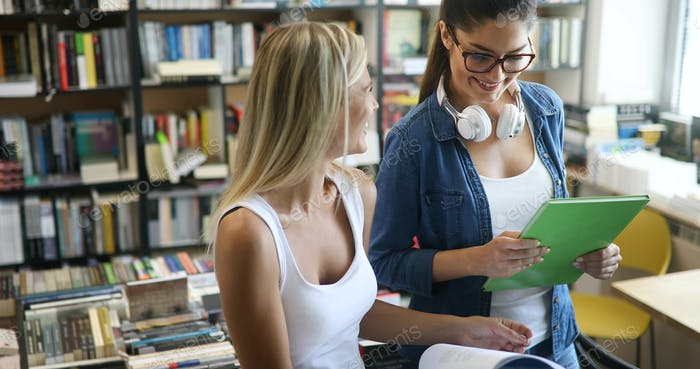 Happy young university students friends studying with books at university