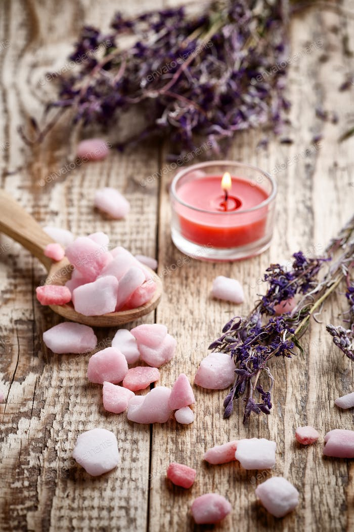 Homeopathic sea salt, lavender dry flowers and wooden surface.
