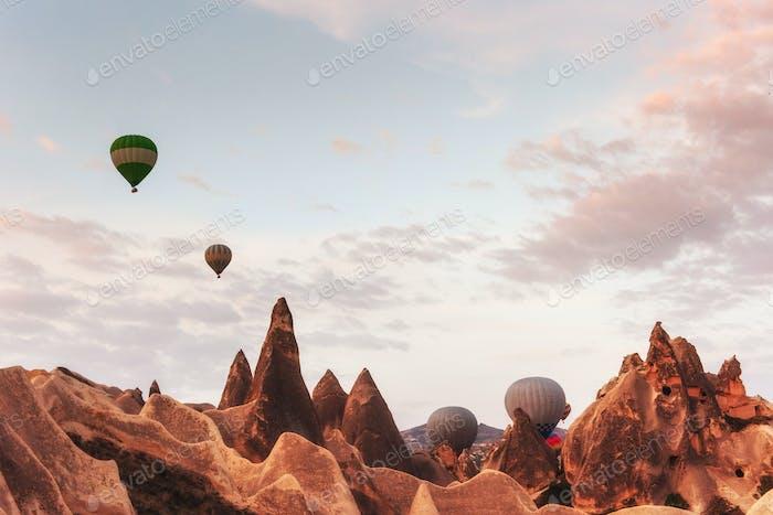 Hot air balloon flying over rock landscape at Cappadocia Turkey.