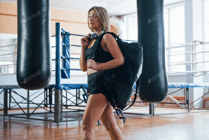 Walks to the garderobe. Adult female with black bag and headphones in the training gym