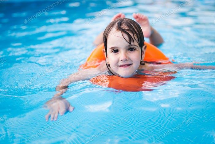 Kleines Mädchen im Schwimmbad mit Schwimmring