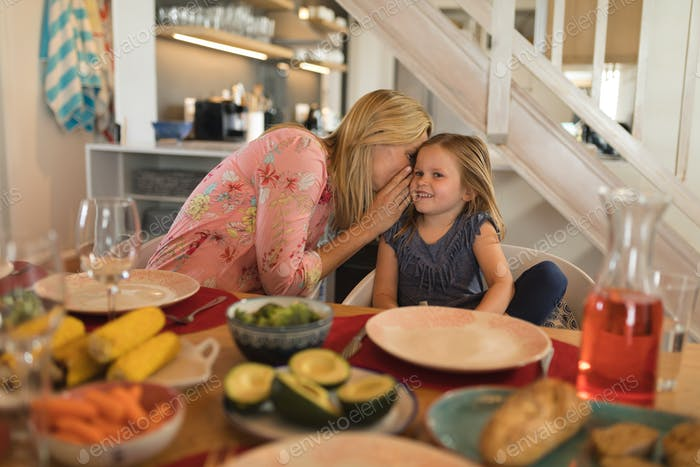 Front view of a mother whispering in daughter ear on dining table at home