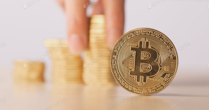 Bitcoin with pile of coin over the back