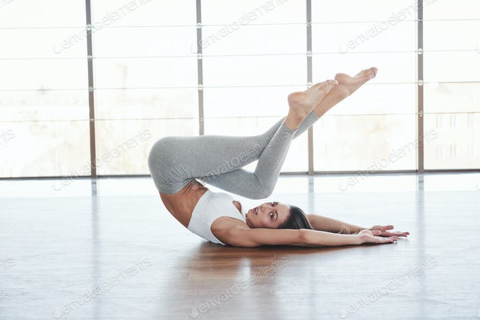 Two legs is up. European young brunette doing yoga in the room with big windows
