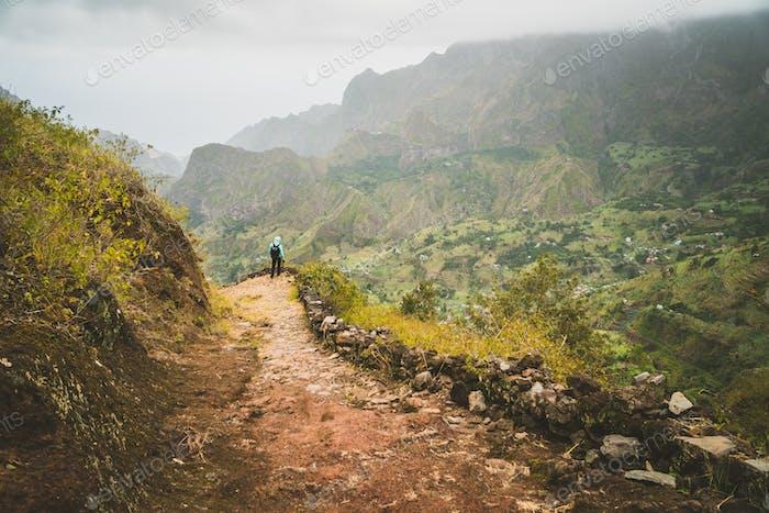 Man enjoying impressive mountainscape. Arid canyon valley extend far below. Santo Antao, Cabo Verde