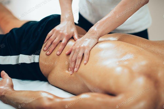 Sports massage. Therapist massaging lower back
