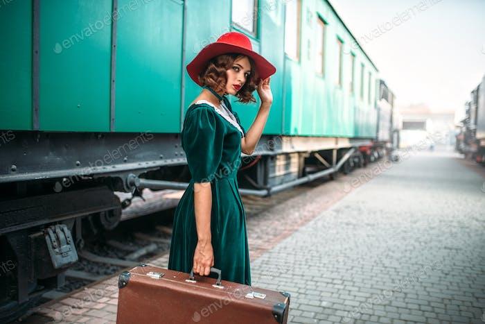 Junge altmodische Frau reist auf Retro-Zug