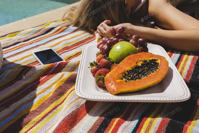 Relaxing by the pool with fresh fruit.