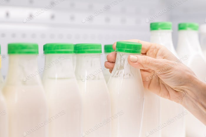 Hands of contemporary mature female consumer taking plastic bottle of kefir