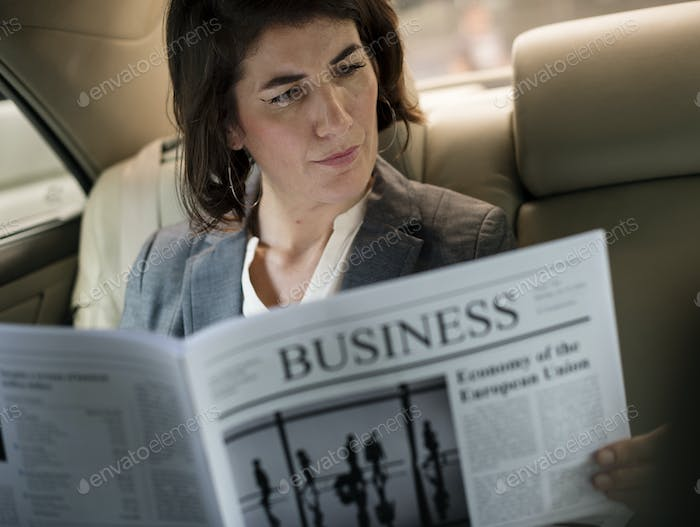 Businesswoman Reading Newspaper Car Inside