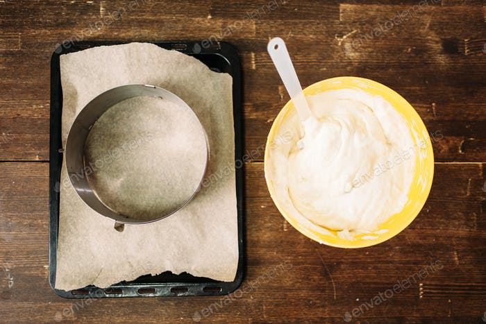 Fresh dough in bowl and pan with parchment paper