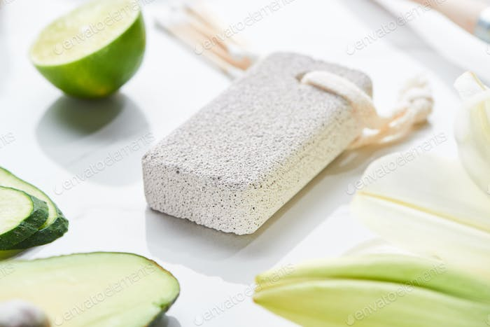 Close up View of Gray Pumice Stone Near Fresh Lime And Cucumber on White Surface
