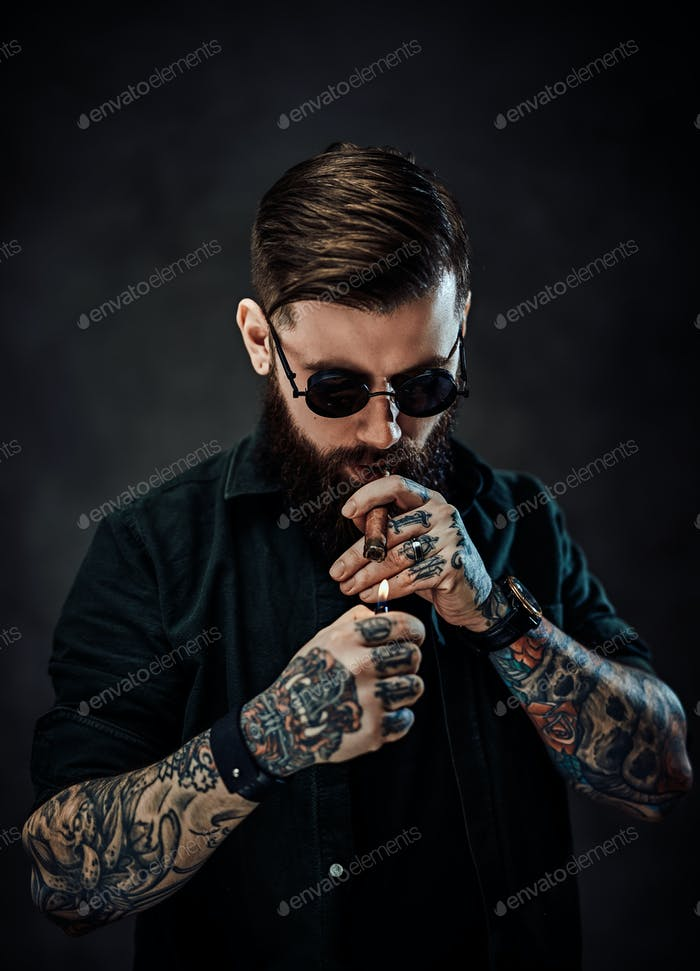 Bearded tattooed guy wearing green shirt and sunglasses lights a cigar