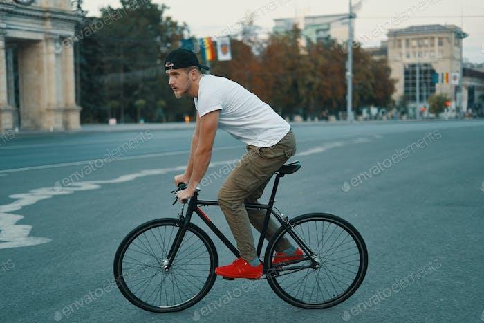 Junge moderne Mann Radfahren auf einem klassischen Fahrrad auf der Stadtstraße