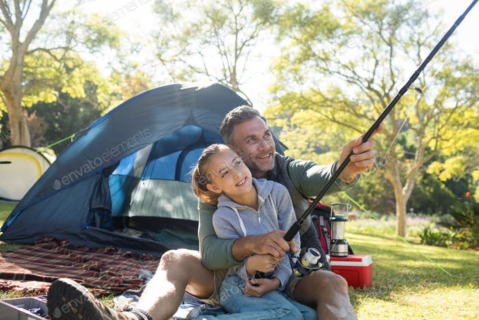 Father and daughter holding a fishing rod outside the tent