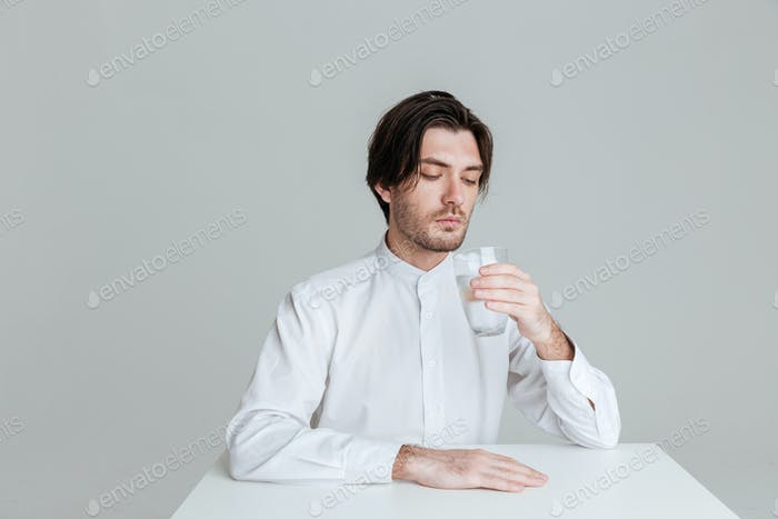 Man drinking from water glass while sitting at the table