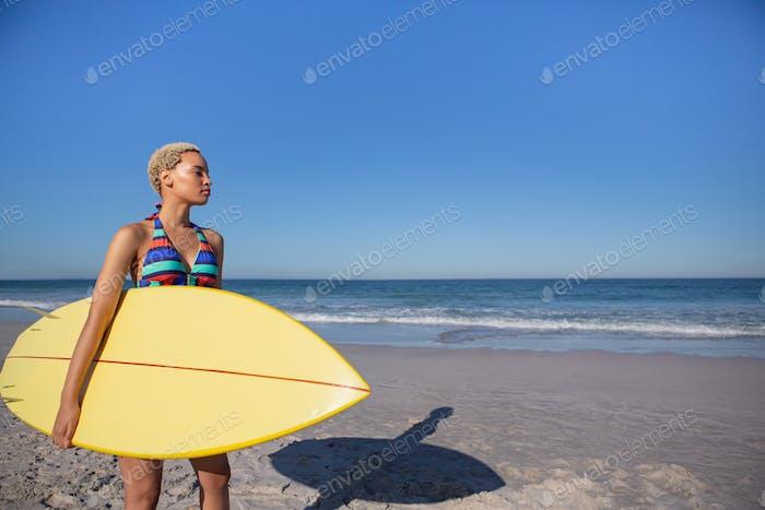 Vorderansicht der Afroamerikanerin im Bikini stehend mit Surfbrett am Strand in der Sonne