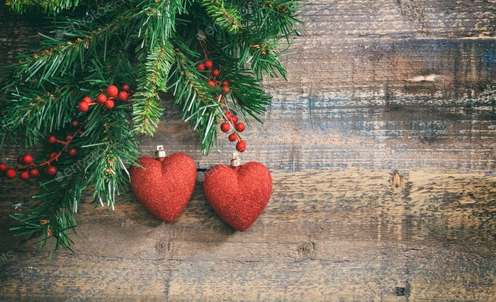 Christmas red hearts and green garland on a wooden board