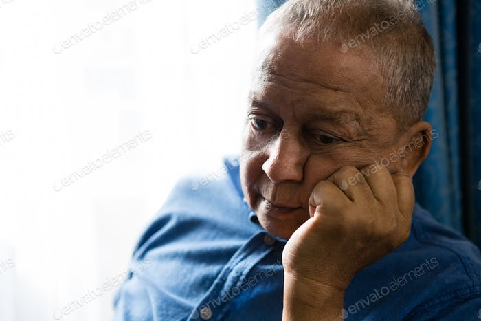 Sad senior man with hand on chin sitting by window