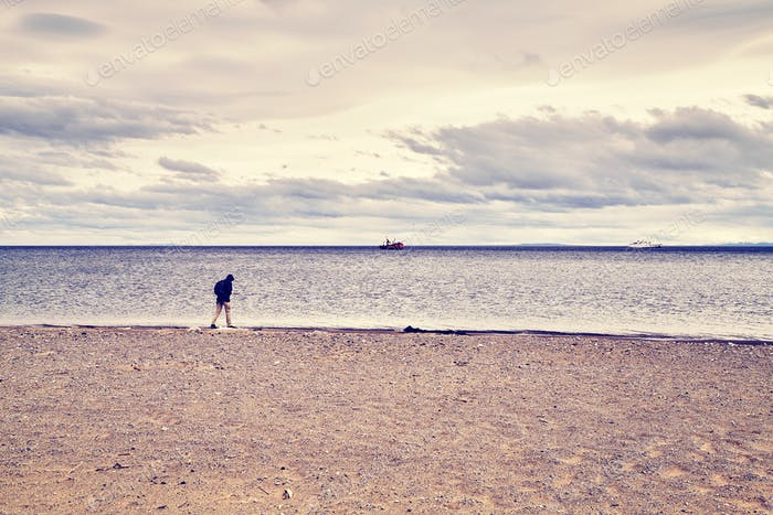 Lonely person walks along a beach.