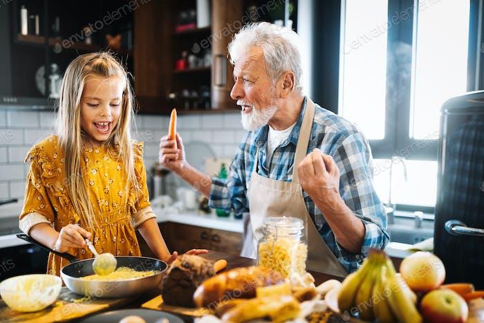 Улыбающийся дедушка помогает детям готовить на кухне
