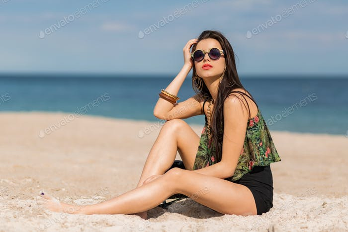 Sexy woman in stylish tropical outfit posing on the beach