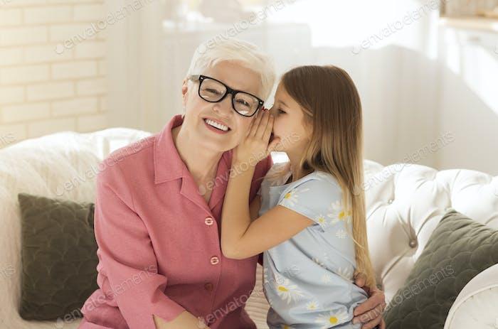 Niedlich Mädchen flüstert etwas zu ihrer Großmutter Ohr im Wohnzimmer