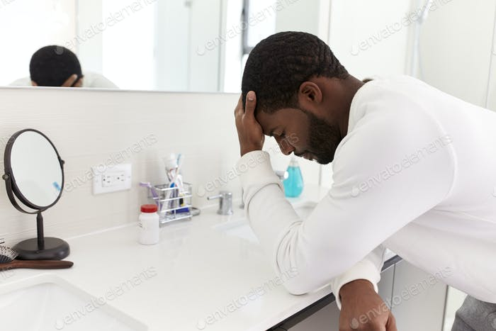 Depressed Man Leaning On Sink In Bathroom With Head In Hands