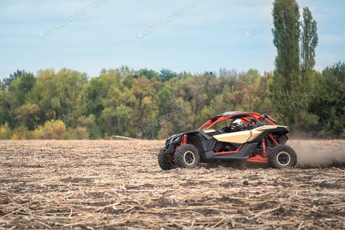 Quad bike is racing at high speed along an oblique field
