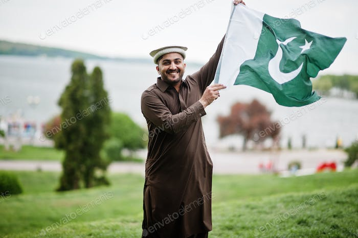 Pakistani pathan man wear traditional clothes hold Pakistan flag.