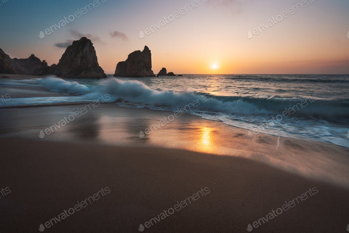 Portugal Ursa Beach at atlantic coast. Sunset reflection. White wave roll towards sandy beach with