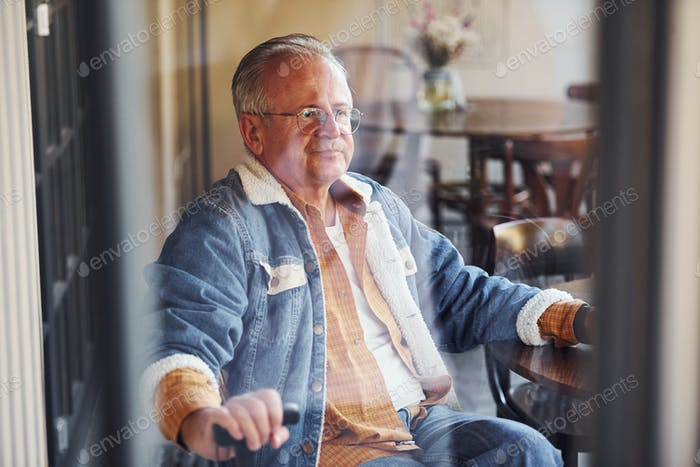 Стильный старший в модной одежде и в очках сидит в кафе