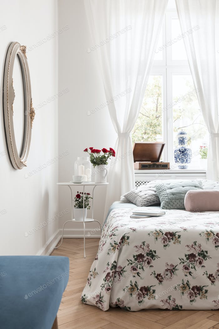 White bedside table with fresh red roses, candles and coffee cup